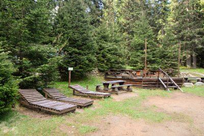 Дървени столове и шезлонги пред хижата